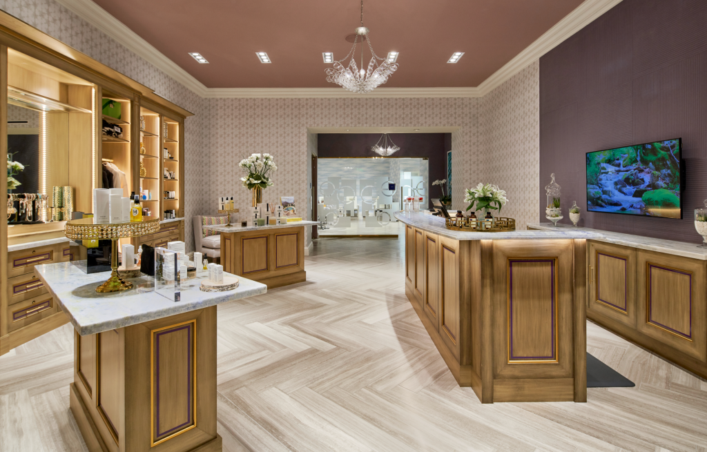 Spa lobby with various spa products displayed in open cabinets and marble topped wood paneled islands
