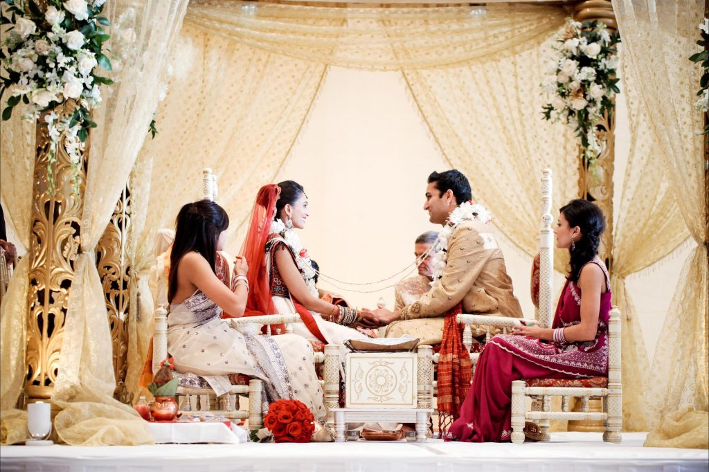 Seated Indian Bride and Groom smiling and holding hands on stage with bridal party surrounded by floral and gold accented pillars and drapes