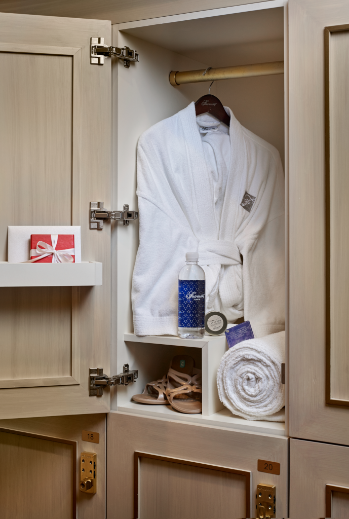 Fine wood locker with polished brass fixtures open showing spa robe hanging, shoe cubby, towel, and complimentary water and gift