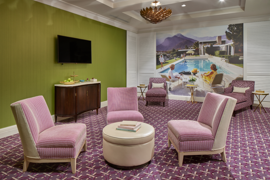 Lounge chairs around a coffee table next to wall with a flatscreen tv, refreshments, and wall with painting of a pool scene