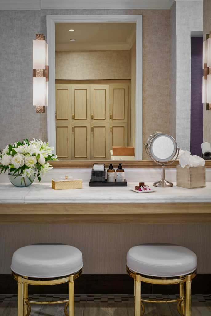 Tall vanity mirror on wall behind a marble topped counter with floral bouquet and personalized spa items