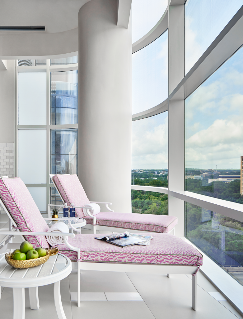 Two lounge chairs with tables of fruit and refreshments facing large wraparound window featuring scenic views