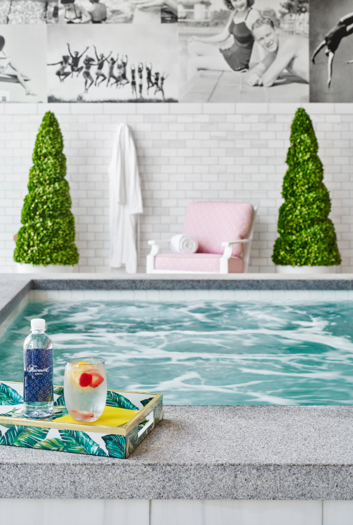 Saline soaking pool with refreshments in a tray in front of a wall with shrubs, robe, lounge chair and nostalgic pool photos