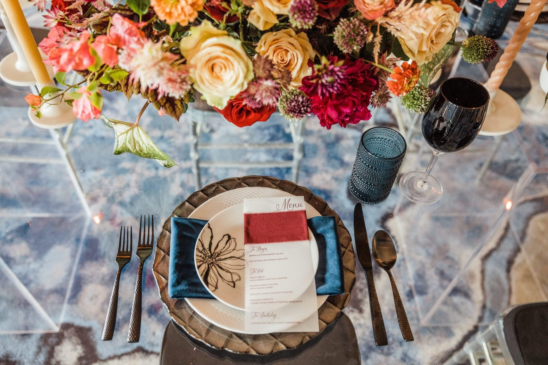 Guest view of elegant place setting, menu, and floral centerpiece looking through all glass dining table