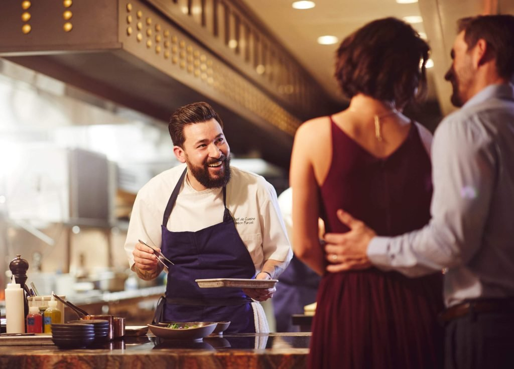 Smiling chef behind marble countertop serving happy couple something delicious with chopsticks and plate