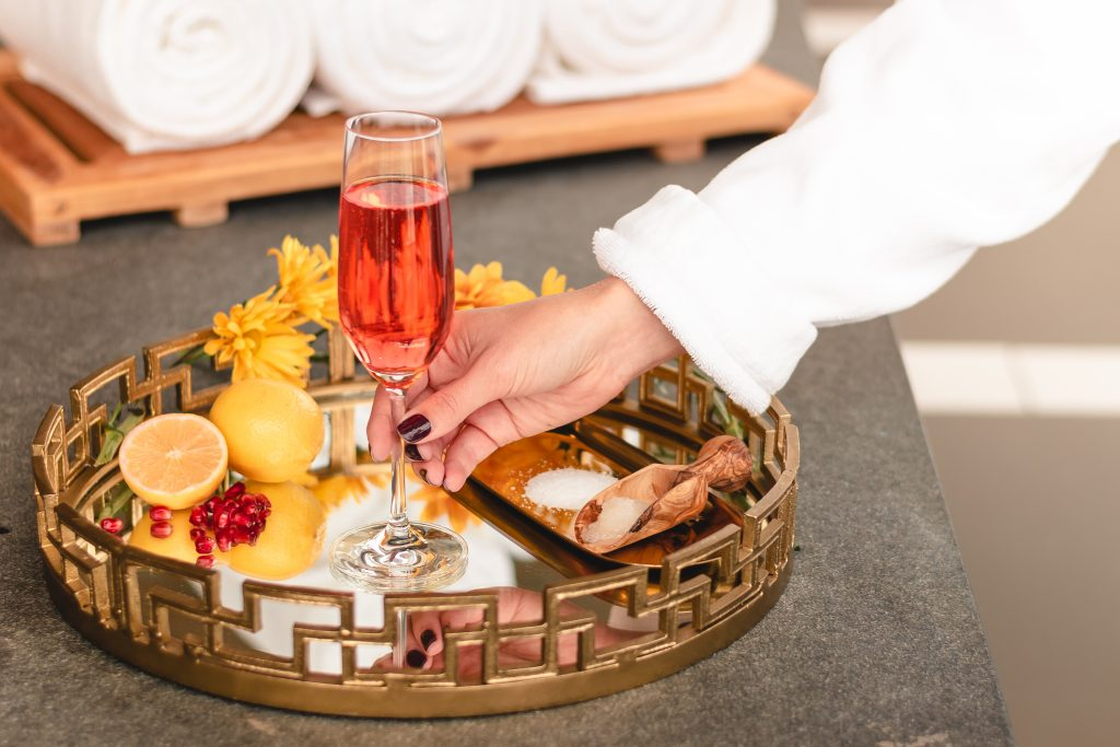 Freshly pedicured robed women's hand taking a champagne flute amongst citrus halves and salt scoop from a mirror bottomed circular tray with intricately patterned brass accent rim
