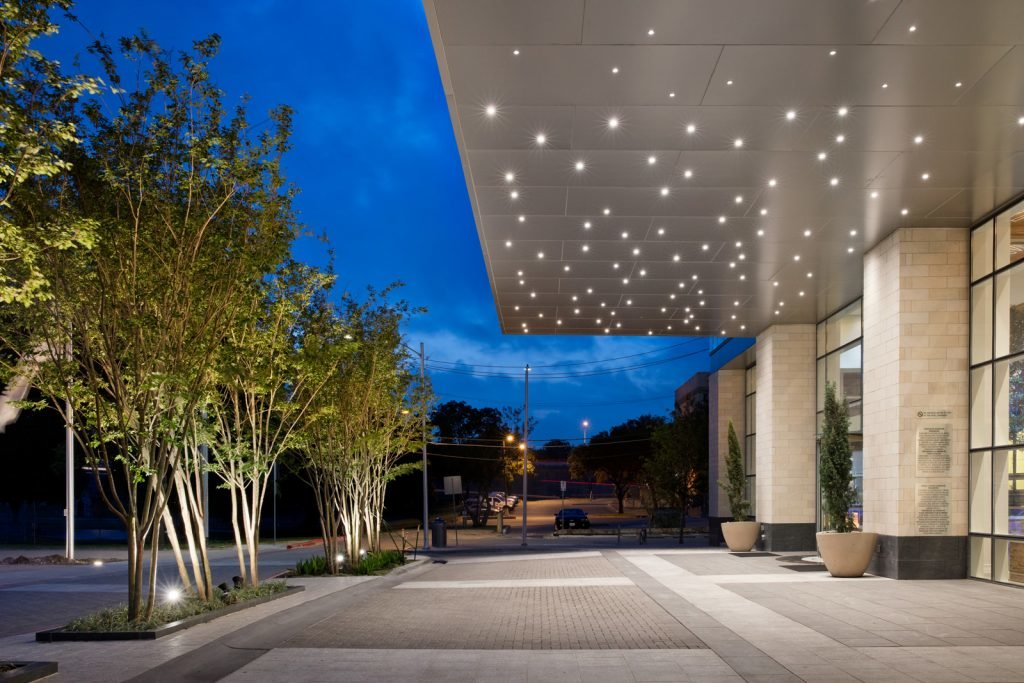 Wide exterior view of covered drive up entrance to lobby looking outwards toward park and evening sky