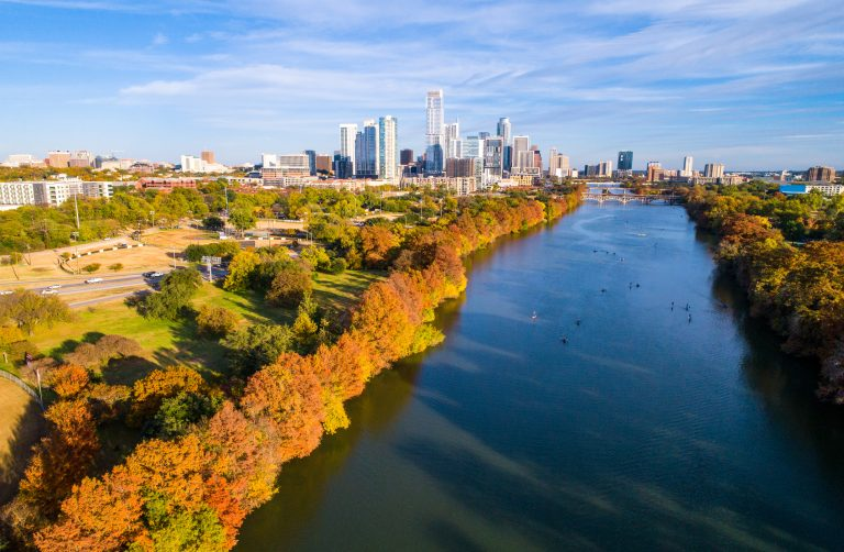 Austin Texas above lady bird lake , as leaves change during autumn fall colors dramatic line of trees along shore with Austin Texas skyline cityscape downtown skyscrapers in background