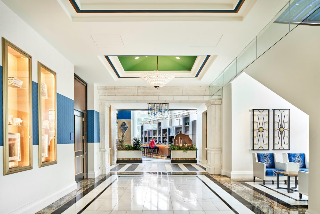 Wide view of lobby with open space with marble floors, in wall glass displays, lounge seating area