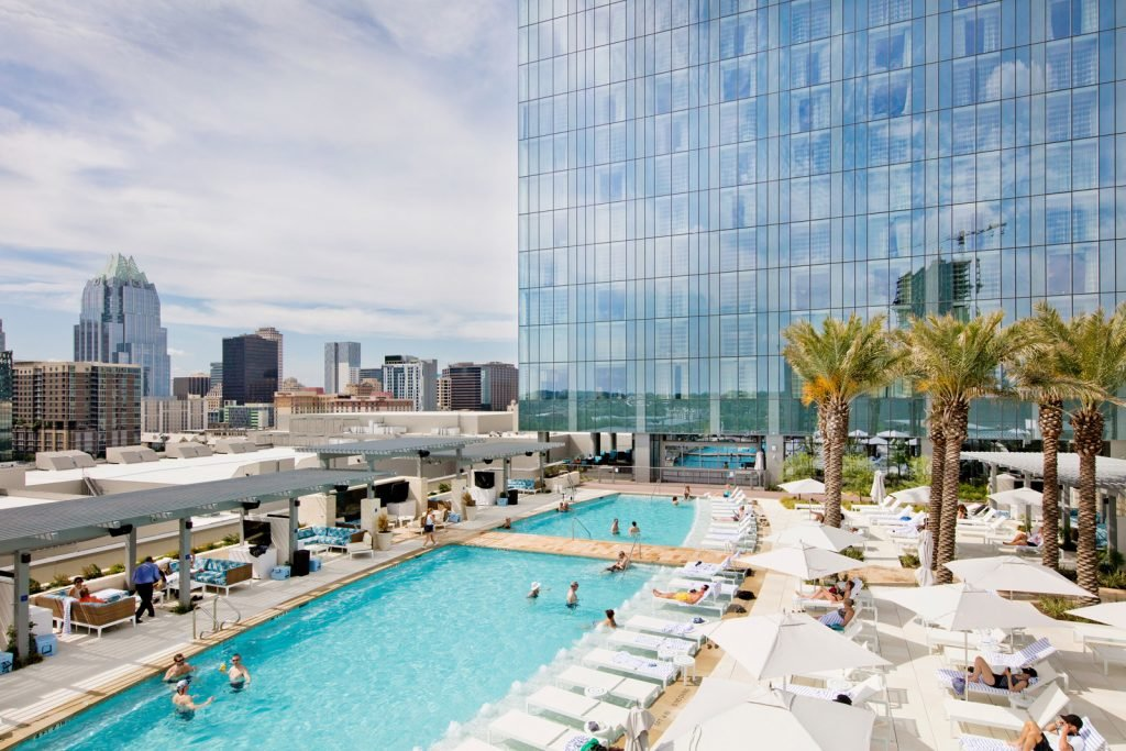 Aerial view of guests enjoying the twin pools with and pool deck with lounge chairs and palm trees with glass exterior reflecting the daytime city skyline