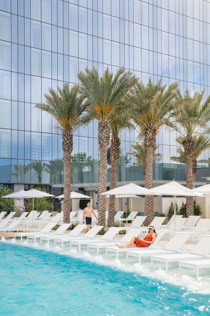 Daytime view of outdoor pool and sparkling water with fountains along the edge of lounge chairs and palm tree with glass exterior in the background