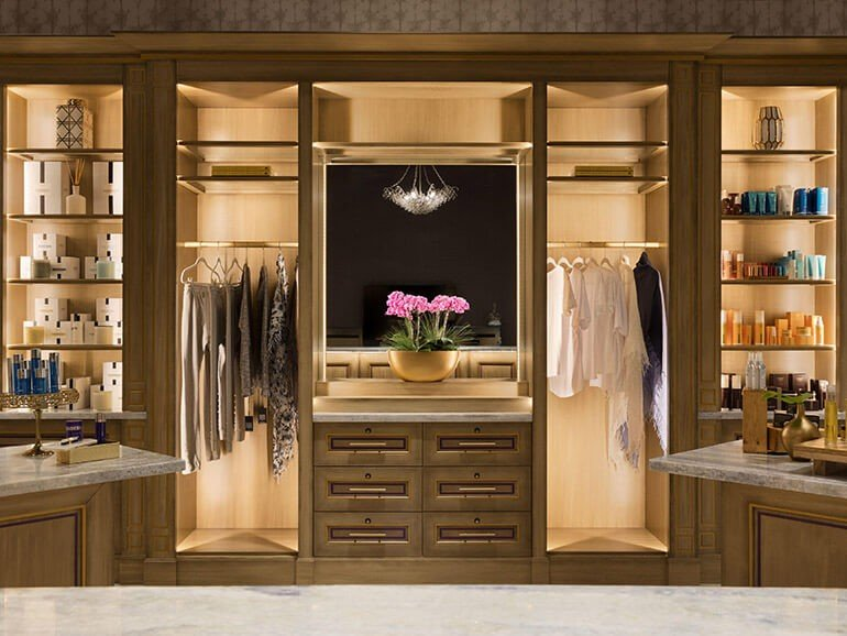 Wall of available spa amenities in lit cabinet in spa lobby