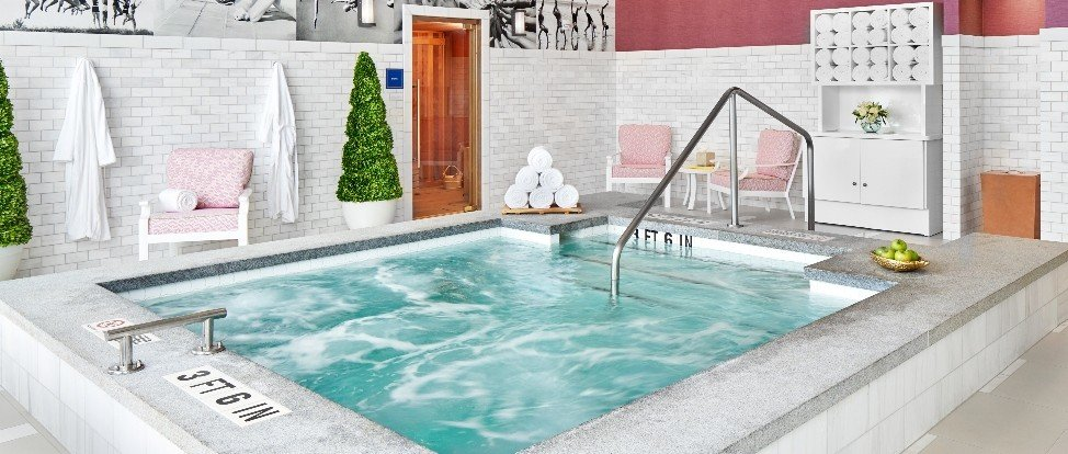 Saline soaking pool with refreshments in a tray in front of a wall with shrubs, robe, lounge chair and towel cabinet