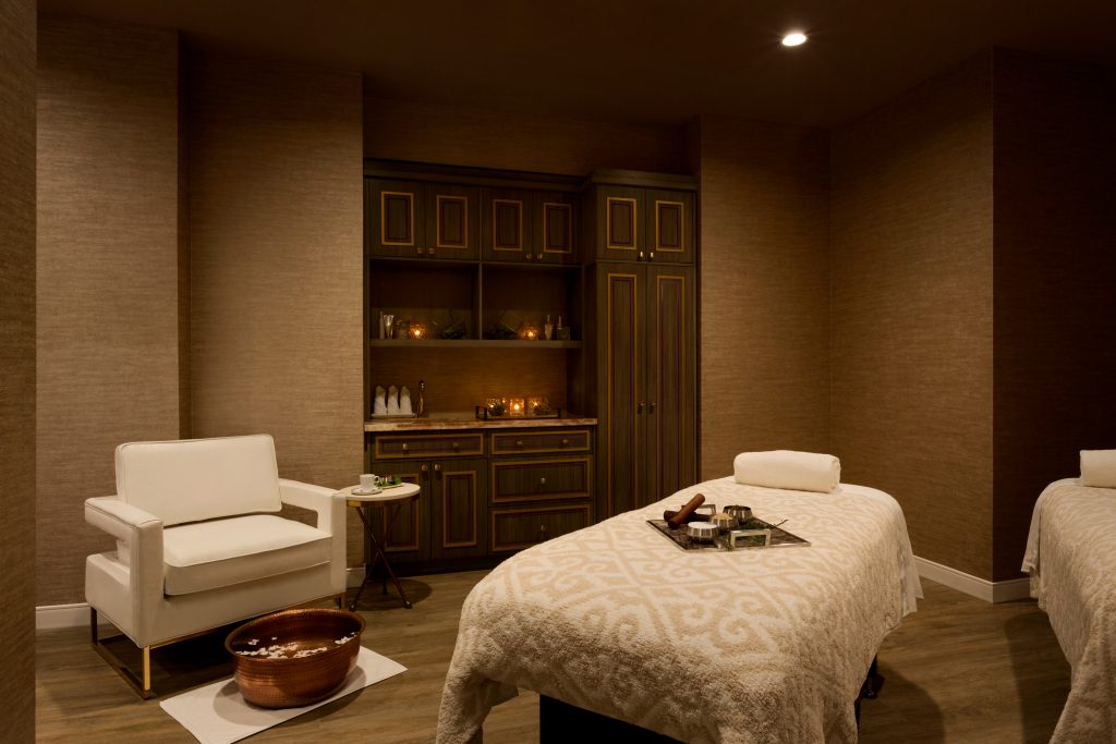 Warmly lit spa treatment room with armchair and foot soaking tub and 2 massage tables with tray of spa treatments