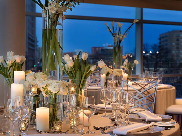 Banquet table and chairs with elegant place settings and tall vases with lilies and evening seen in large widow in background