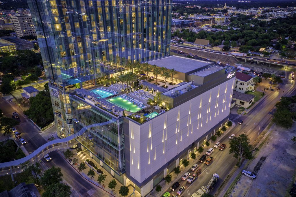 Nighttime exterior view of Fairmont Austin and pool deck and surrounding downtown area