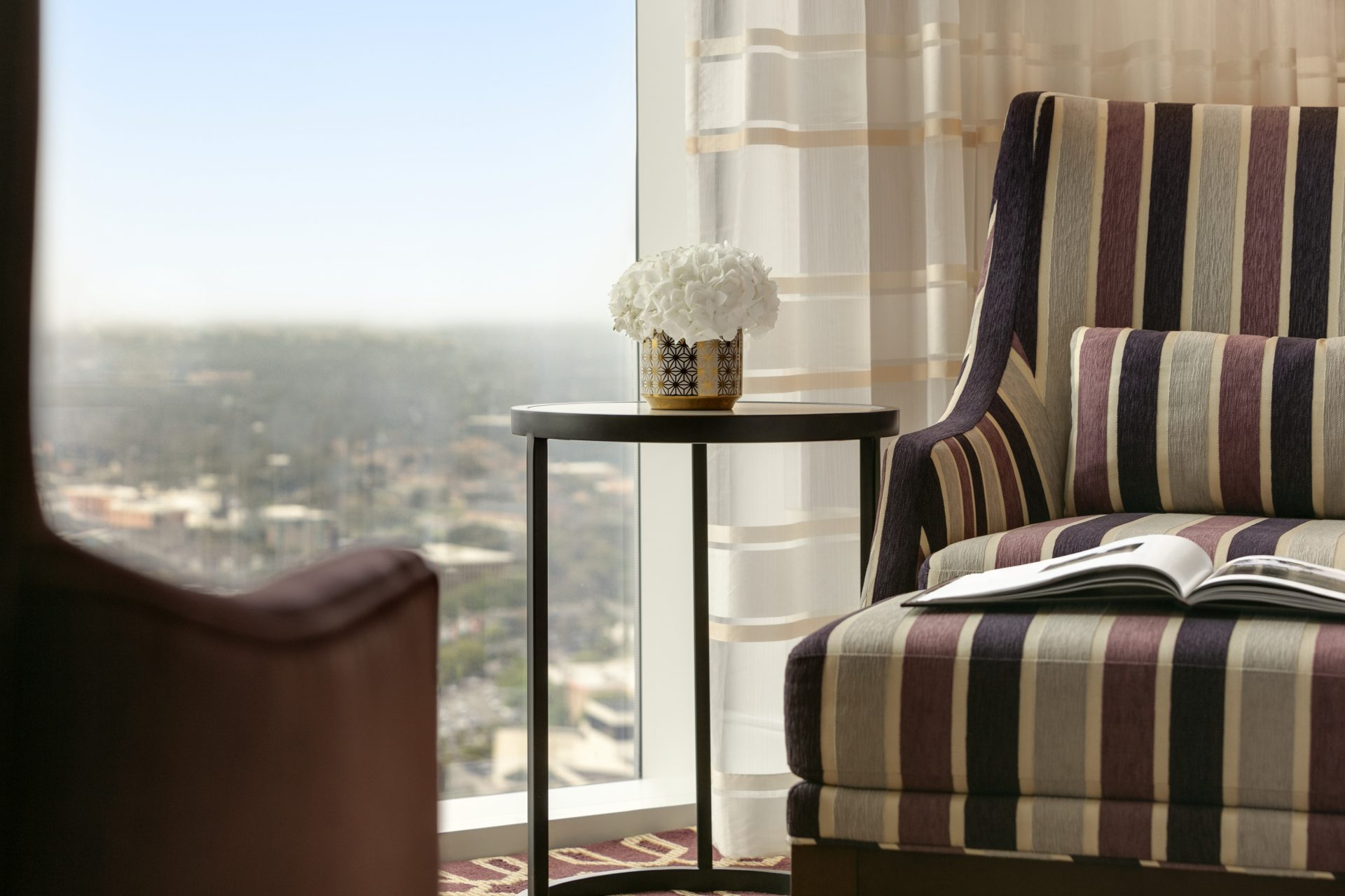 Close up view armchair and small table next to large window with scenic city view