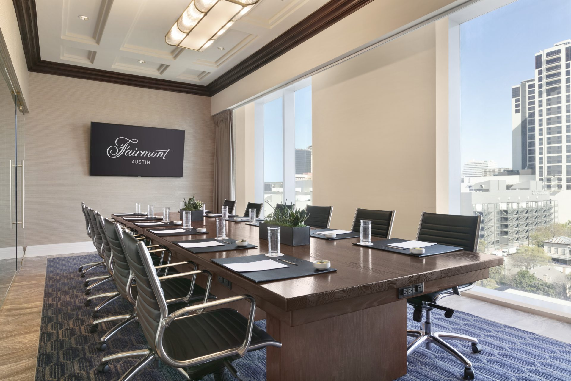 Boardroom with conference table and rolling leather chairs with large flatscreen and large window cityscape views