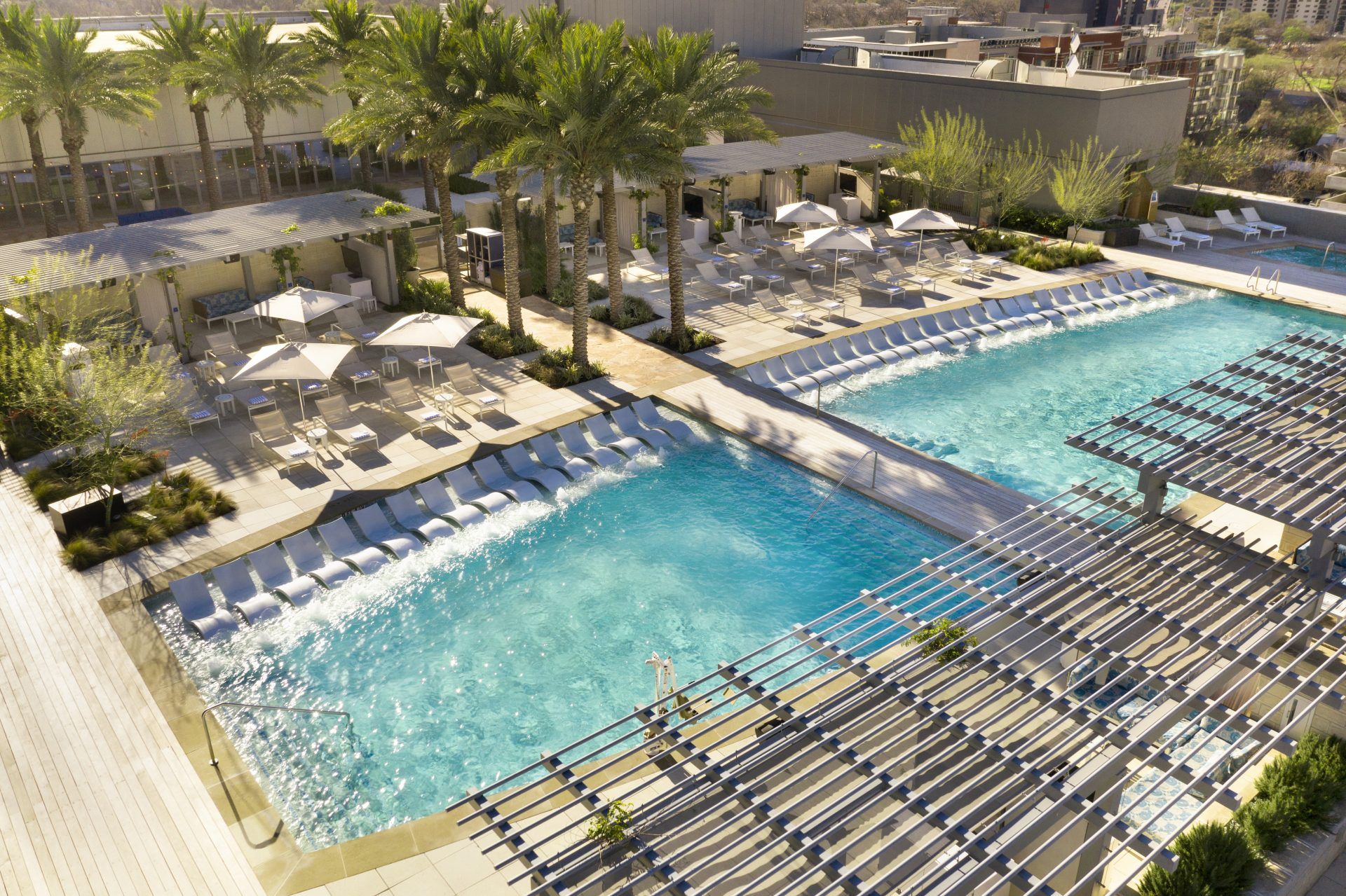 Aerial view of twin pools and pool deck with lounge chairs and palm trees
