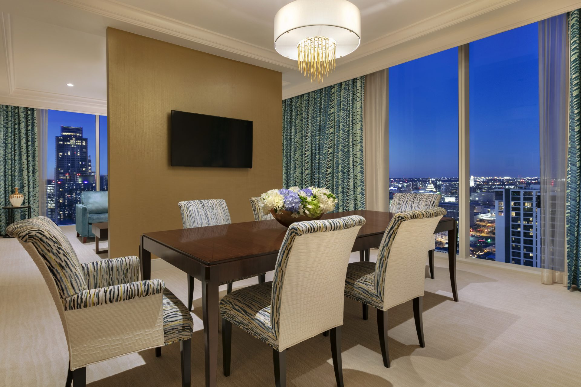 Dining area with large wood table with 6 chairs, floral bouquet, flatscreen wall separating living room all with wraparound city views