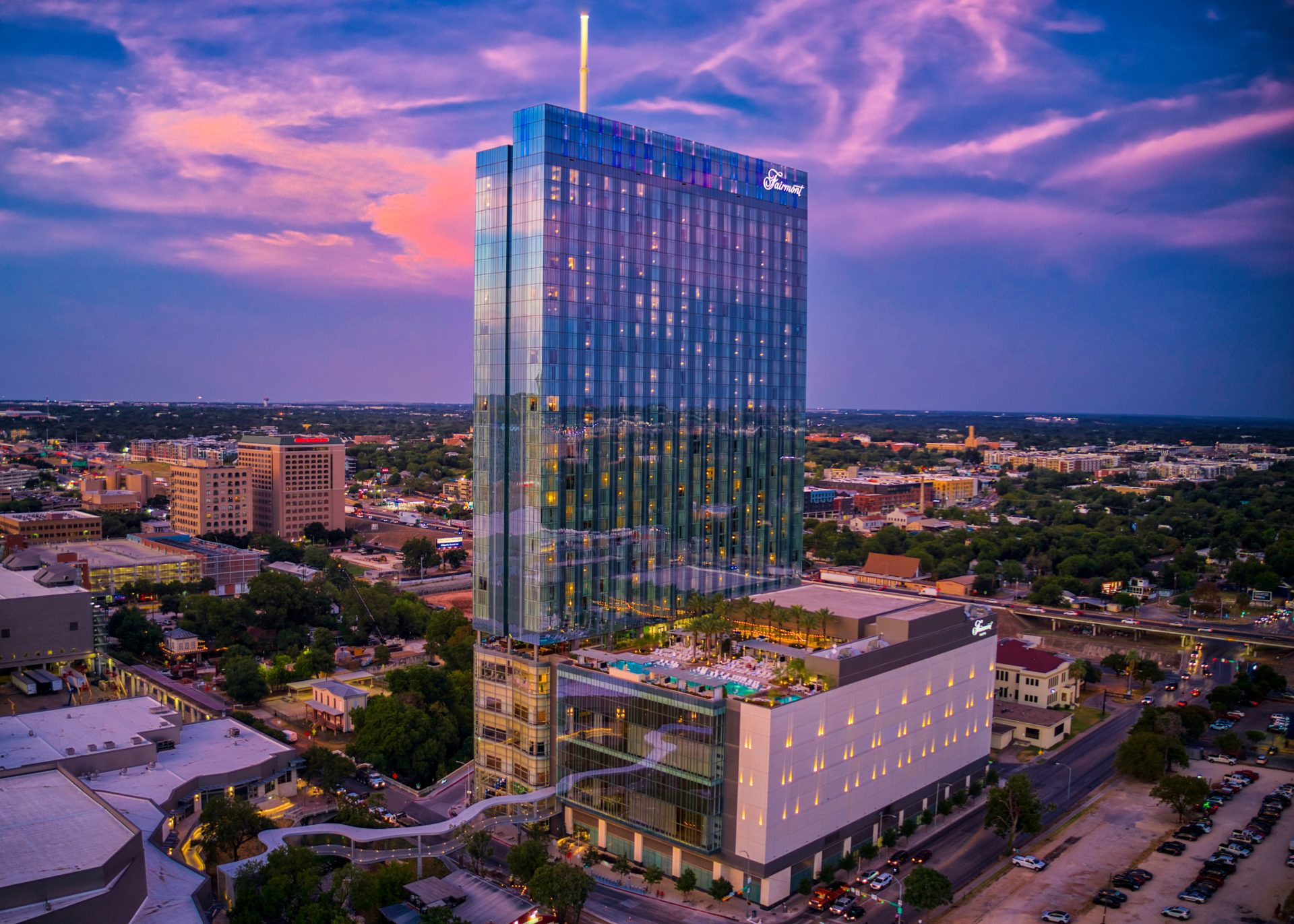 Twilight exterior view of the Faimont Austin reflecting the scenic city