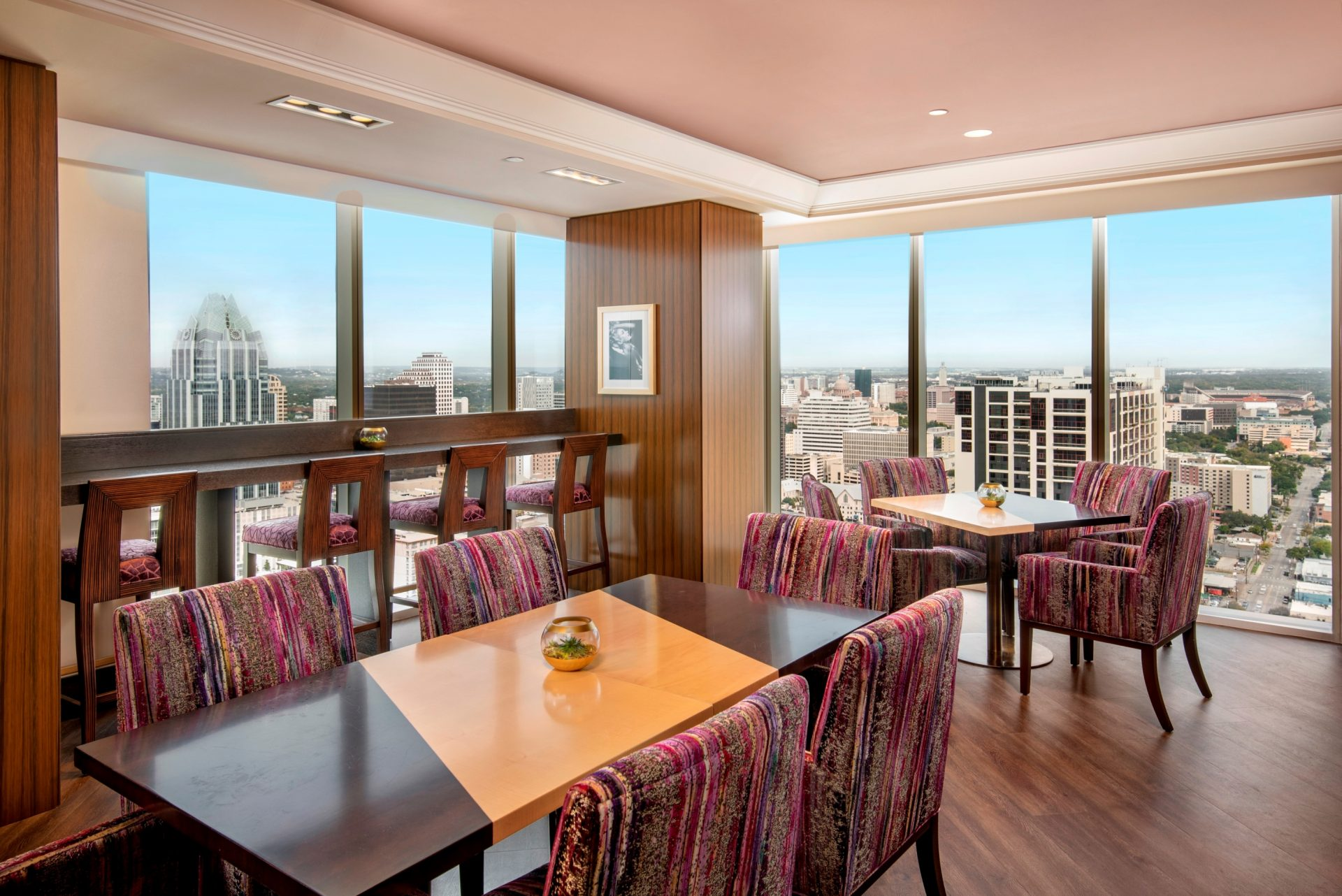 Luxurious lounge with Groups of 4 tables and 4 stools and bar along window featuring amazing city views
