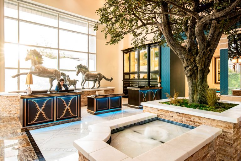 High ceilinged concierge reception area in lobby with fountain, indoor tree, and 3 large metal horse sculptures in front of large window