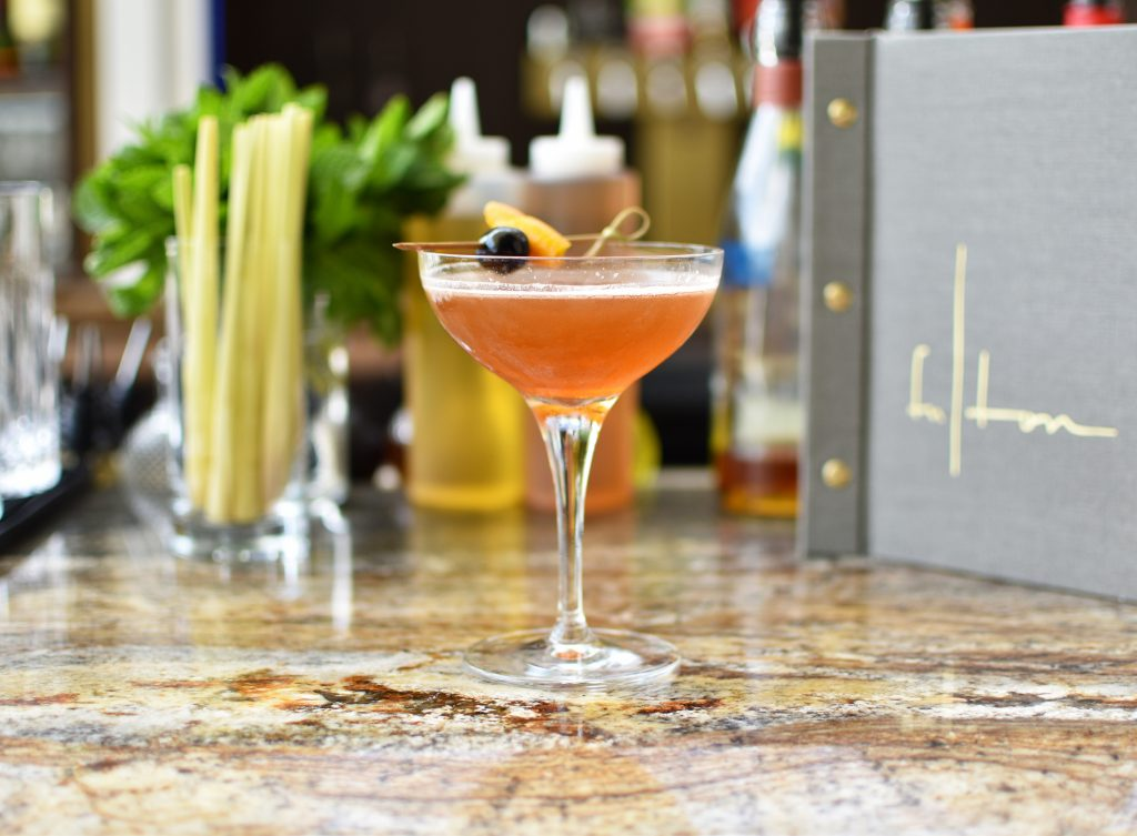 Close up of Hill of Life cocktail in tall wide glass on a marble counter with Fulton menu and bar in the background