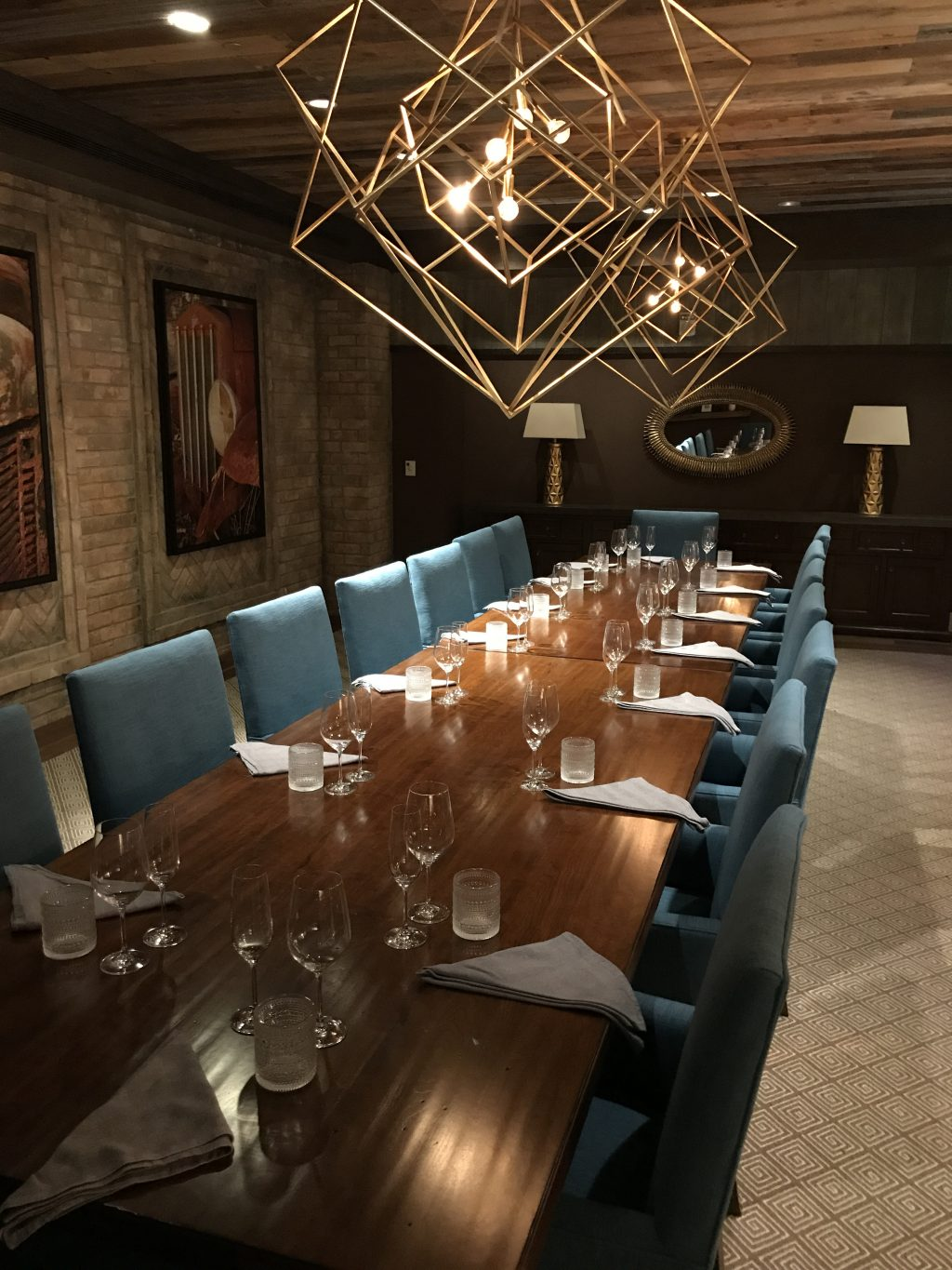 Garrison personal dining room with long wood table and place settings and geometric shaped brass tube chandeliers
