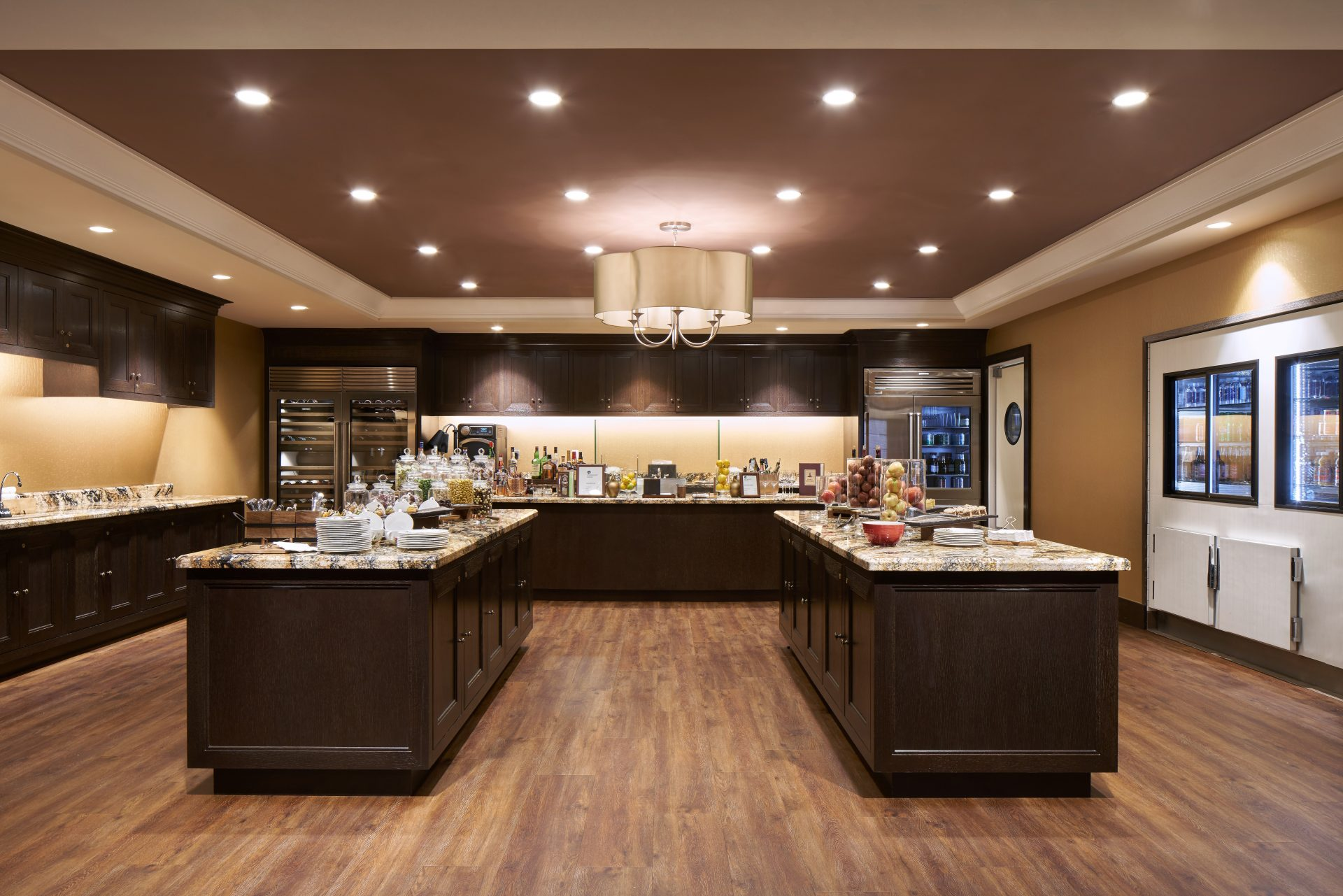 Wide view of elegant buffet style kitchen with 2 long marble topped island and wrap around marble counter with cabinets
