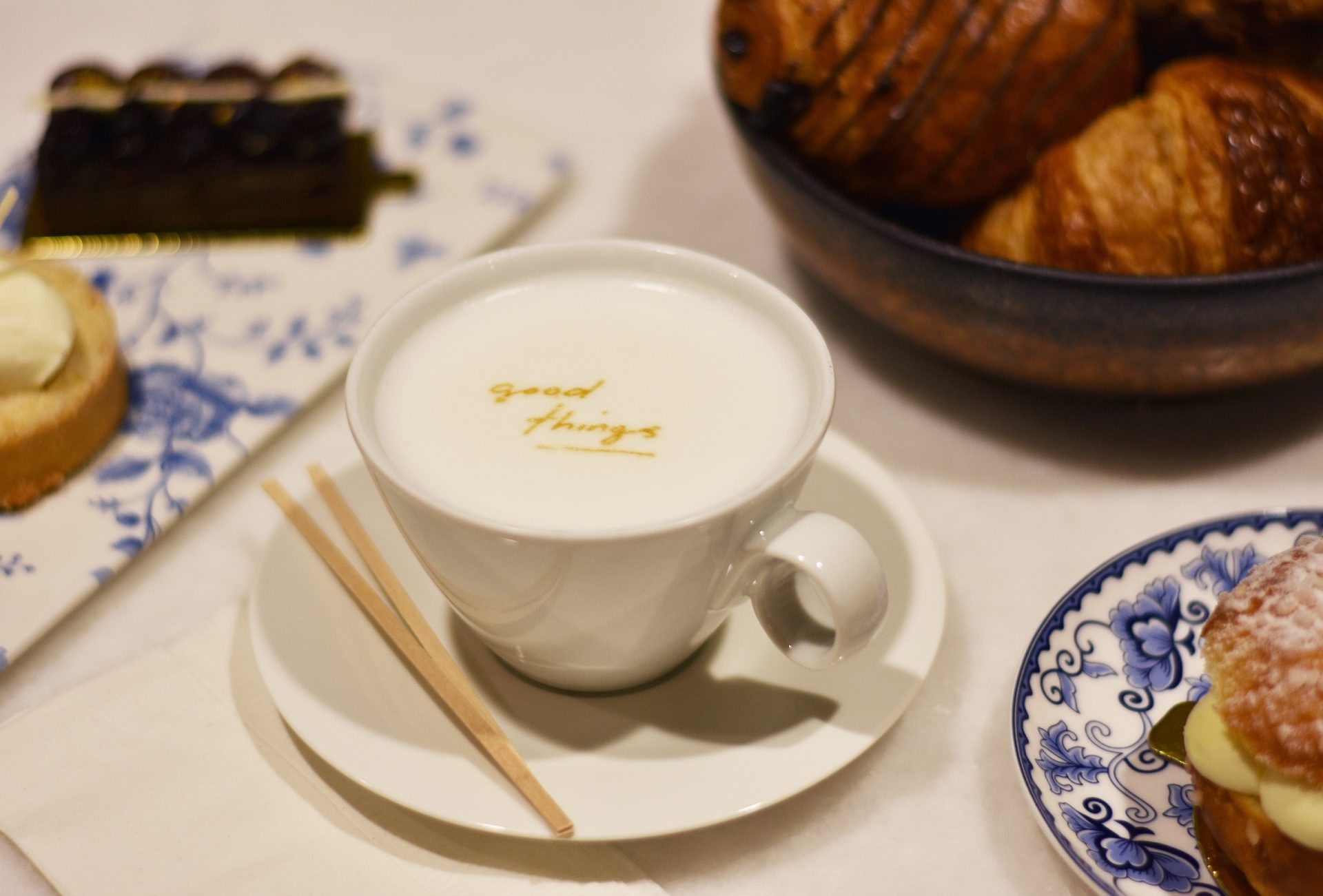Coffee with Good Things logo showing delicately in the cream surrounded by desserts and pastries
