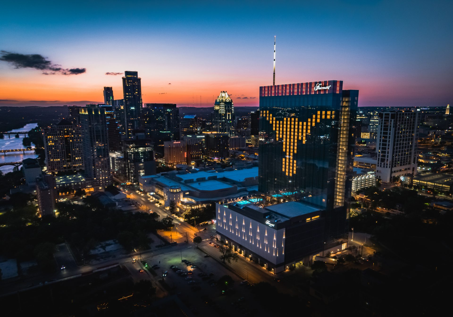 Night aerial view of downtown and Fairmont Austin with rooms lights lit to make the shape of texas athletics mascot