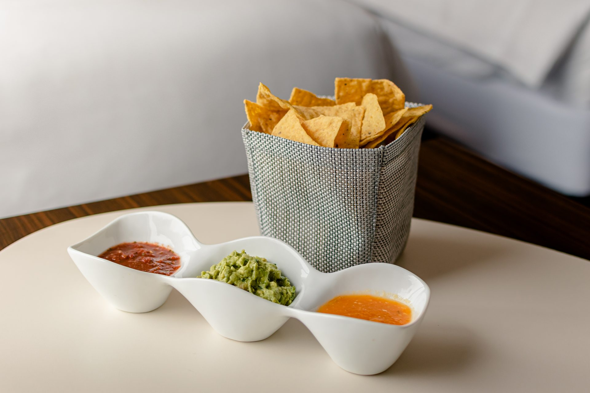 Close up of tortilla chips in woven bag along with ceramic dish with 2 dipping sauces and guacamole
