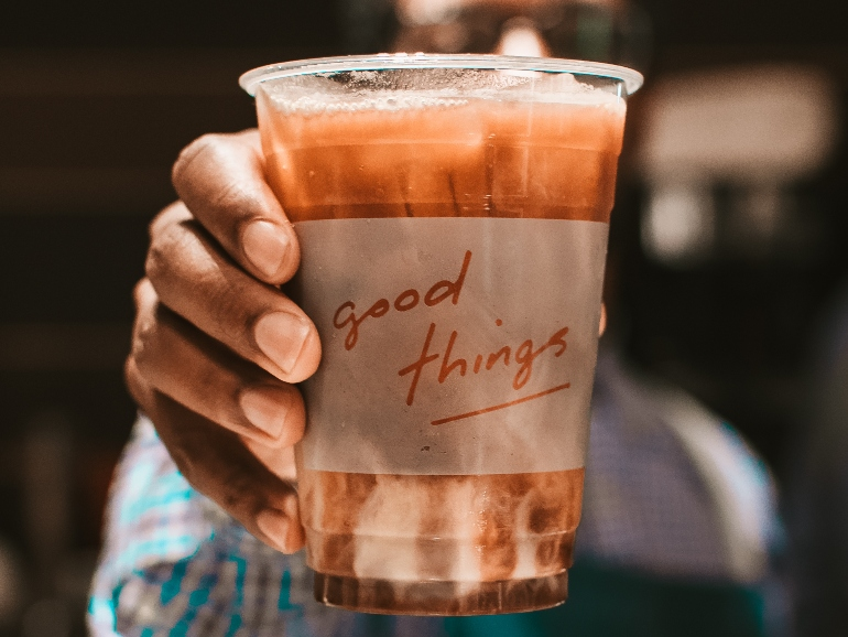 Hand holding fresh brewed iced coffee in clear plastic cup with Good Thing logo