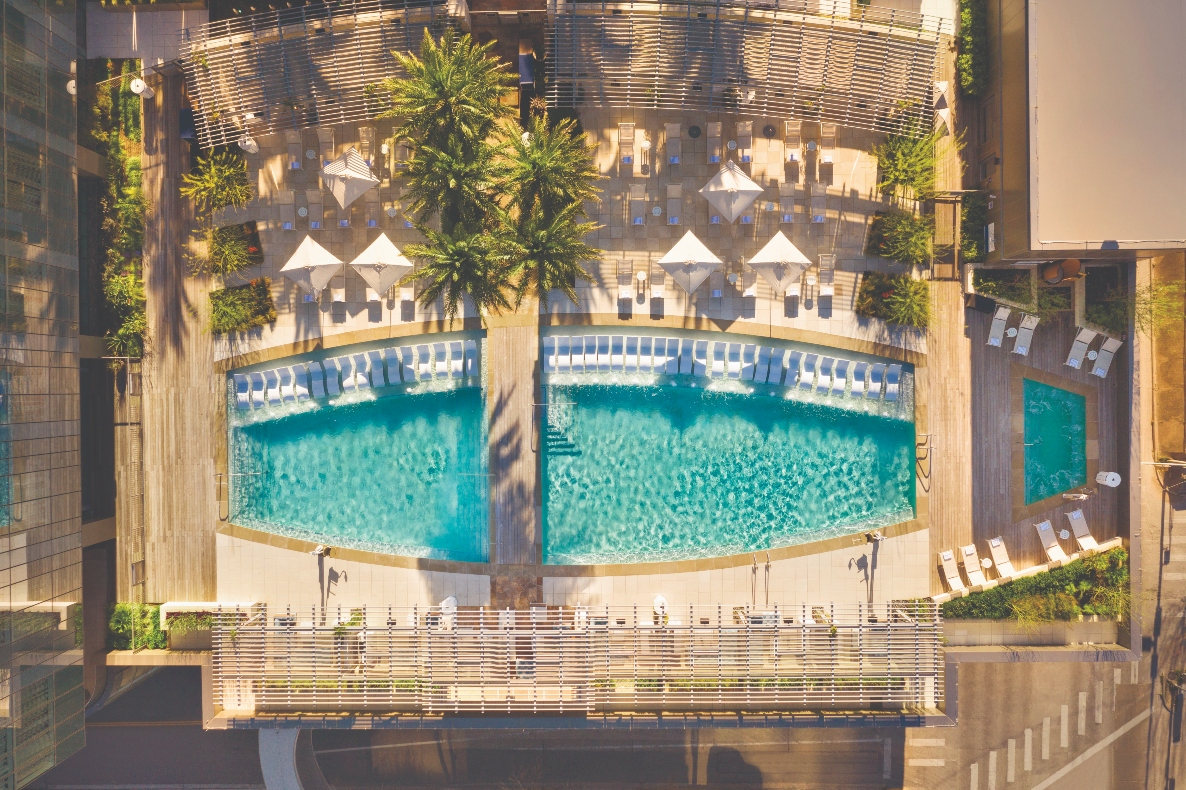 Aerial overhead view of twin pools and pool deck with lounge chairs and palm trees