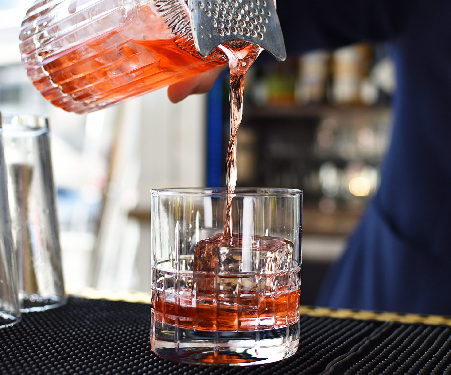 Close up of bartender pouring freshly mixed cocktail into short glass with large ice cube