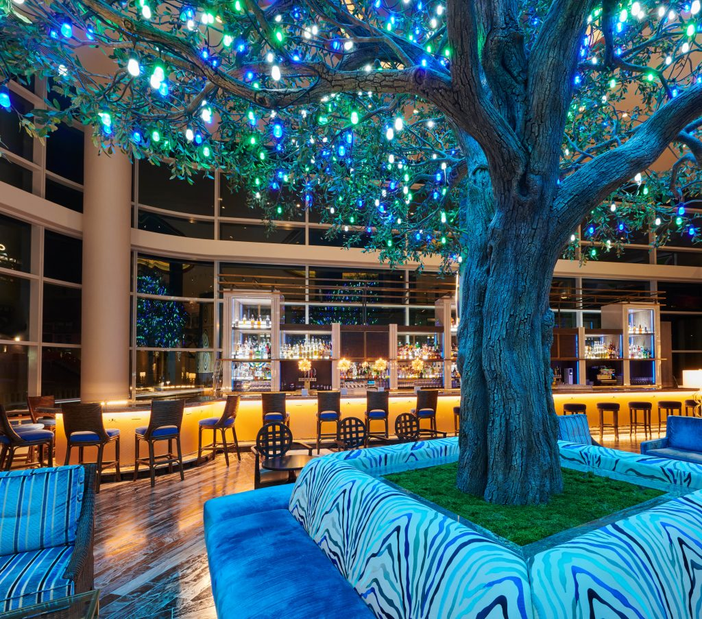 Colorful bright lights in the leaves the large tree in with wraparound seating with expansive bar and large nighttime view of city