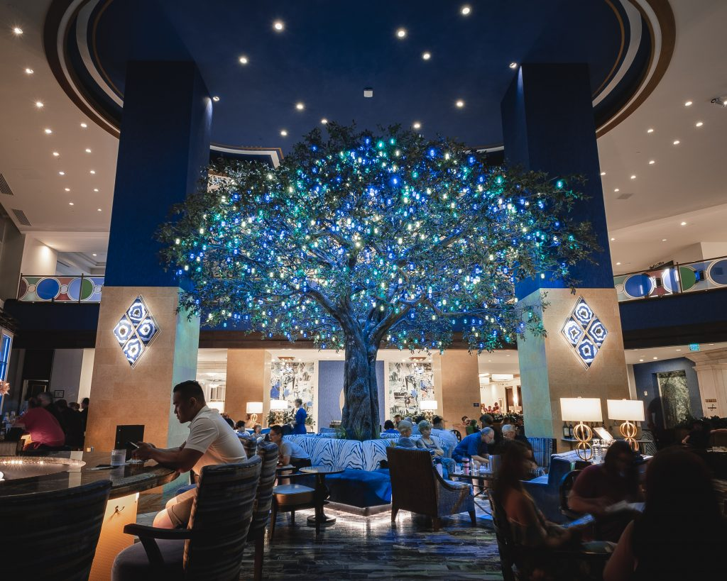 Wide view of the colorfully lit tree in the center of the Fulton lobby bar with guests seated in the bar and dining area