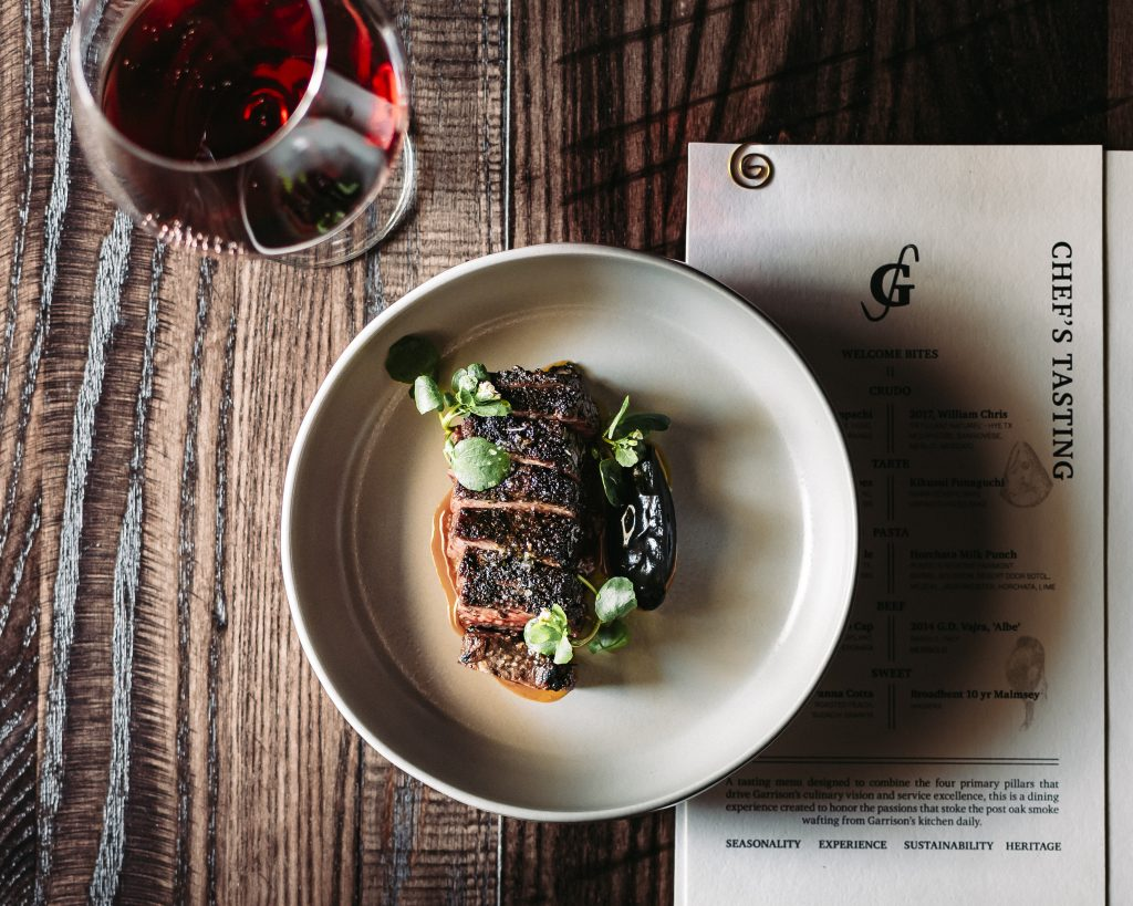 Overhead view of Wagyu beef rib cap on a platter on dark stained wood with Chef's Tasting menu and glass of red wine