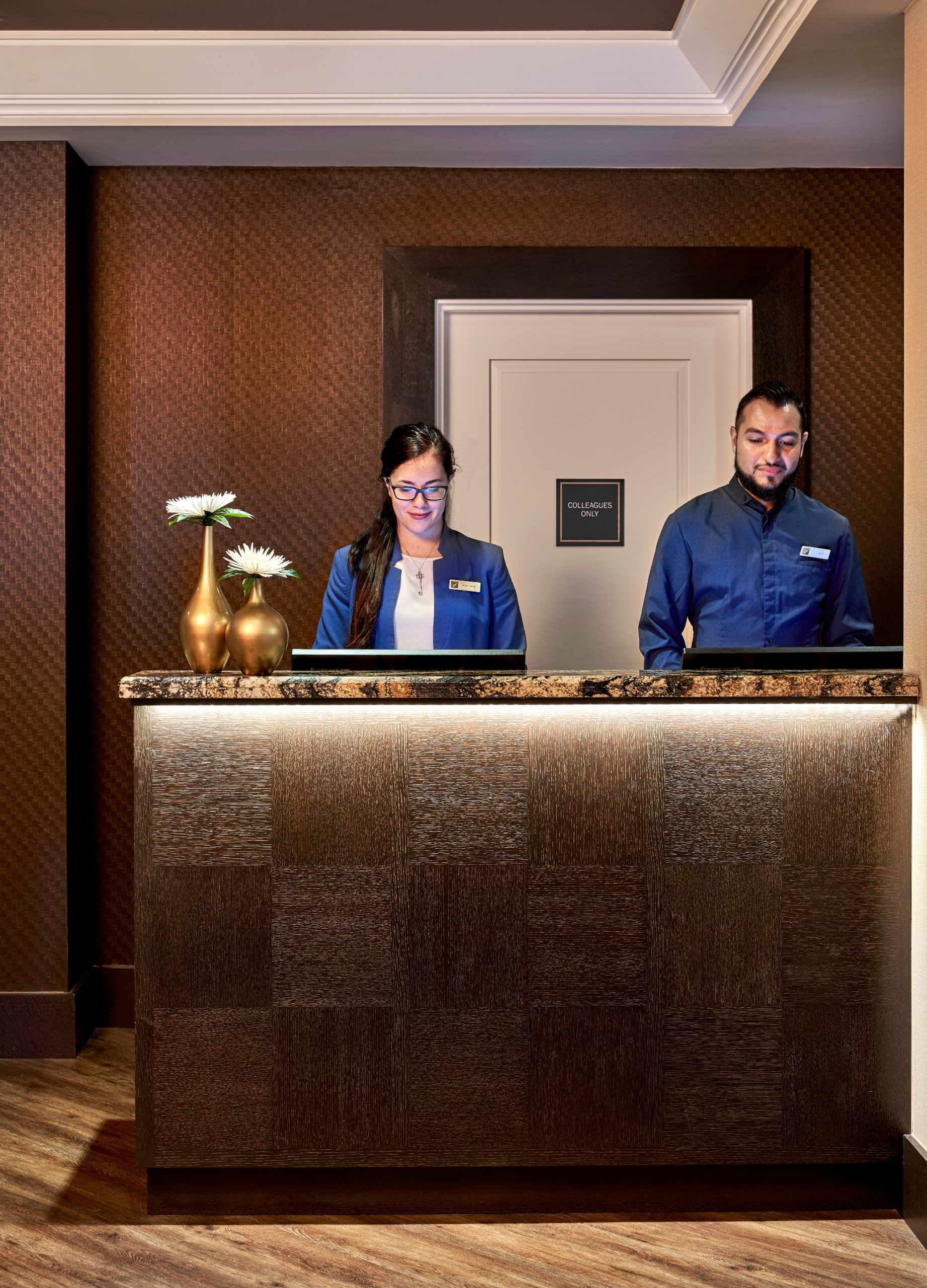 2 smiling concierges behind marble topped brushed gold check in counter
