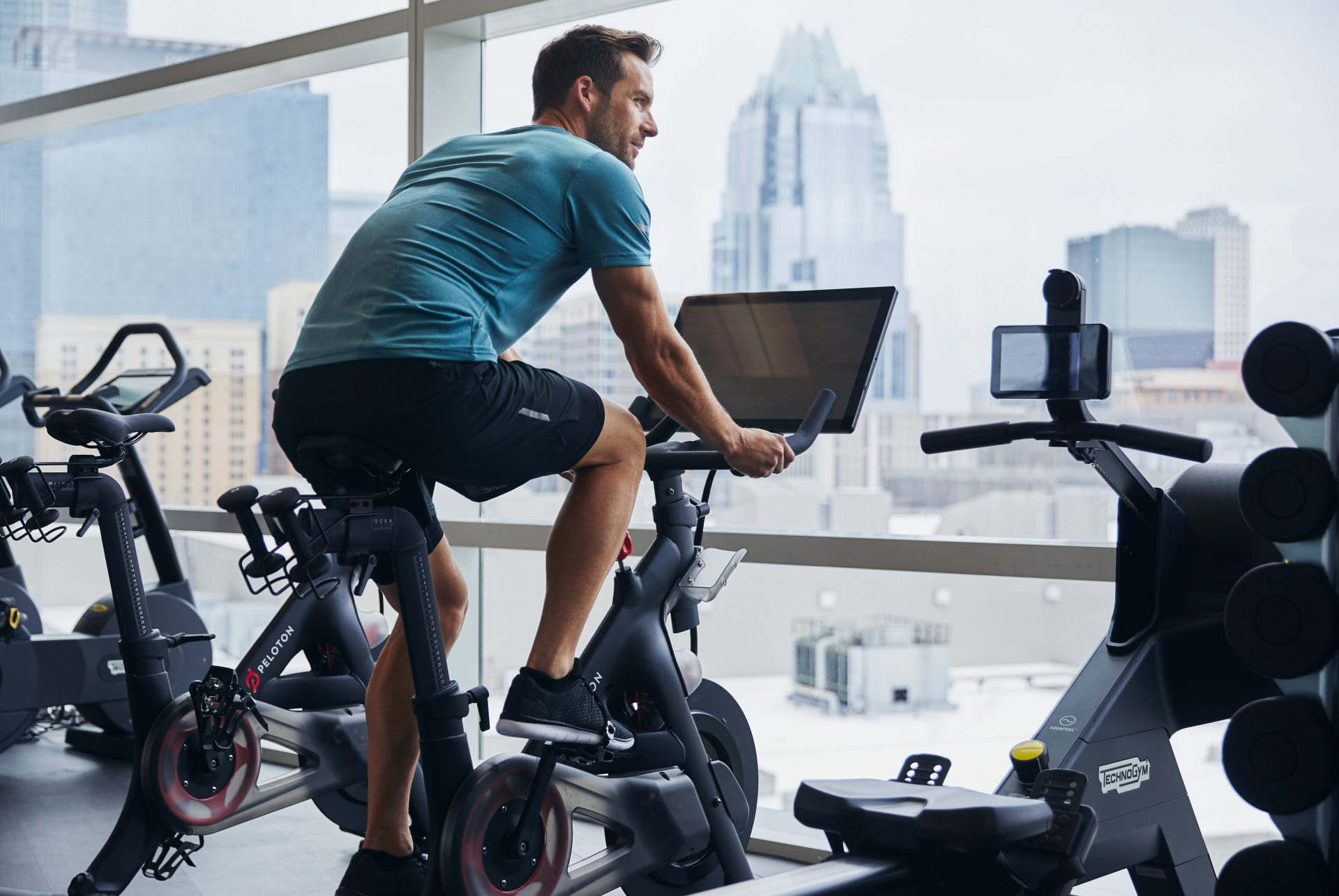 Man cycling on Peleton exercise bike looking out large window with view of downtown buildings