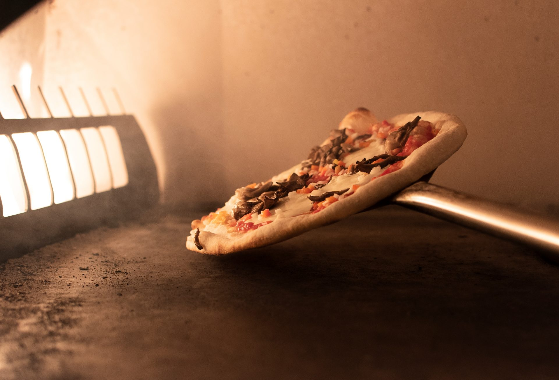 Close up of hand-crafted pizza being placed near burners inside oven