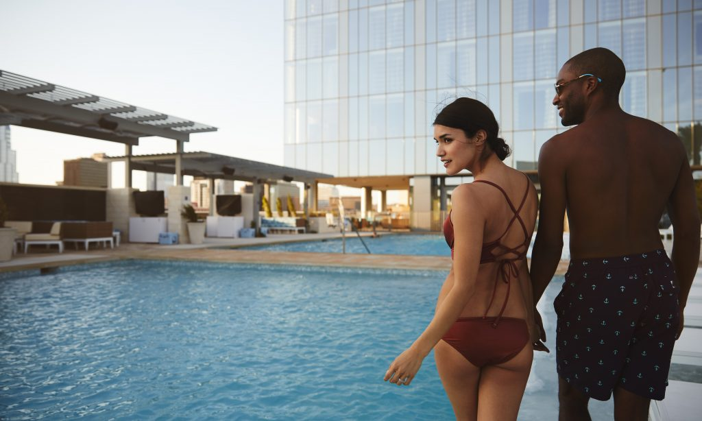 Loving couple wearing swimwear walking along pool deck with deck area, 2 pools and Fairmont Austin glass exterior rising in the background