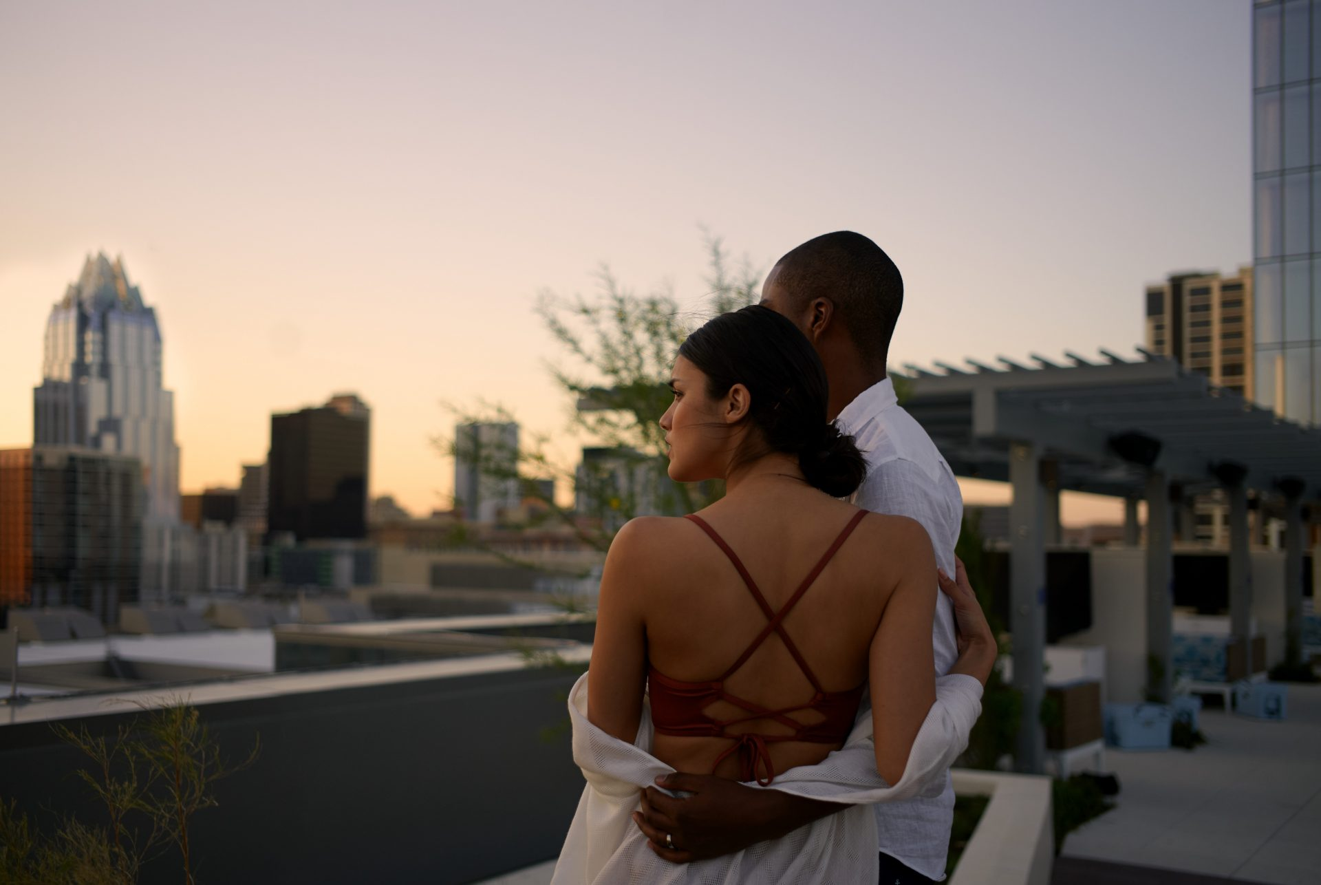 Loving couple embracing while looking out to the scenic skyline city view form the outdoor pool deck area