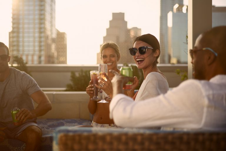 Smiling people toasting to celebrate Bachelor/Bachelorette Party on patio at sunset