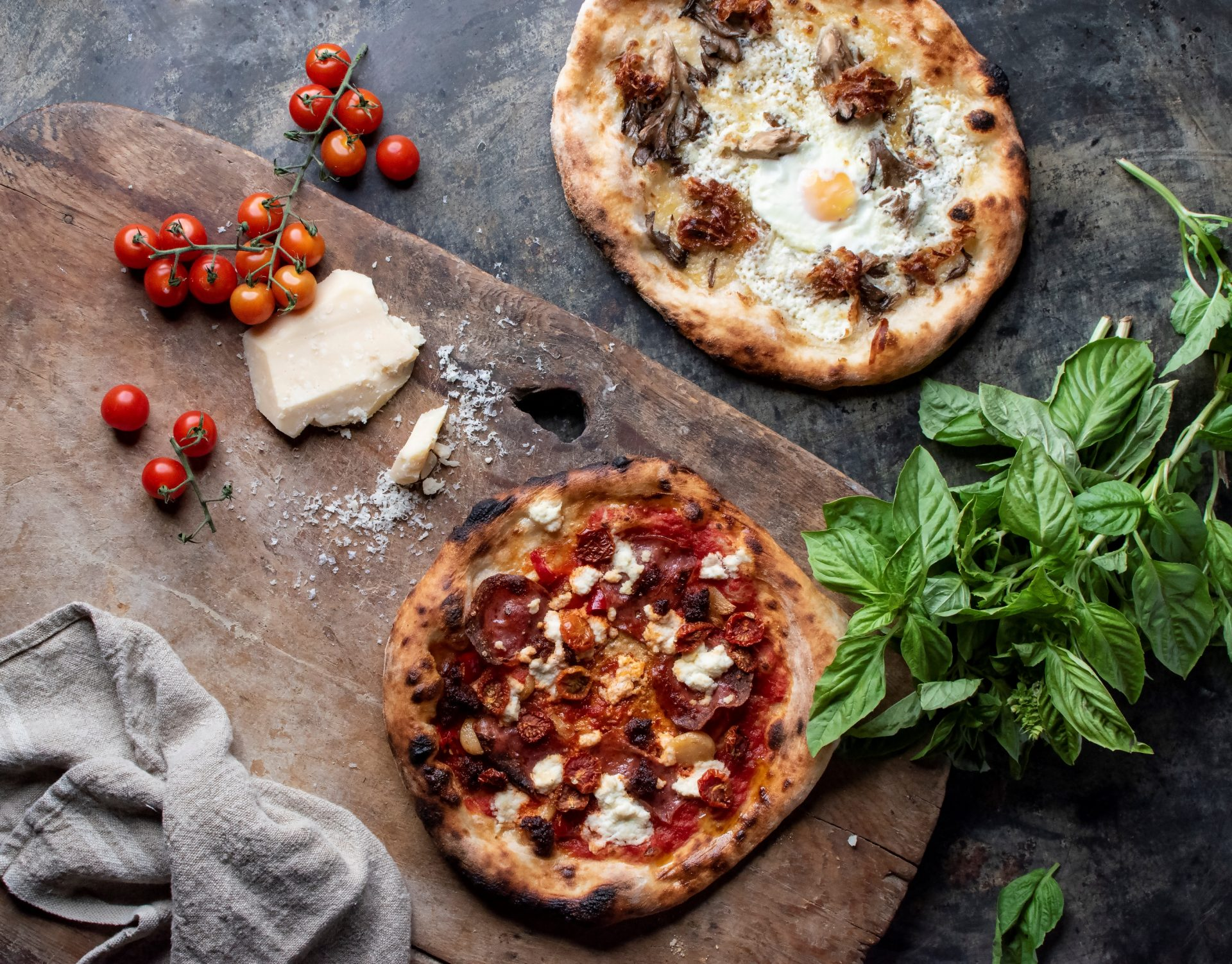 Overhead view of 2 handcrafted pizzas on wooden oven tray with fresh parmesan, vine tomatoes and stalk of herbs