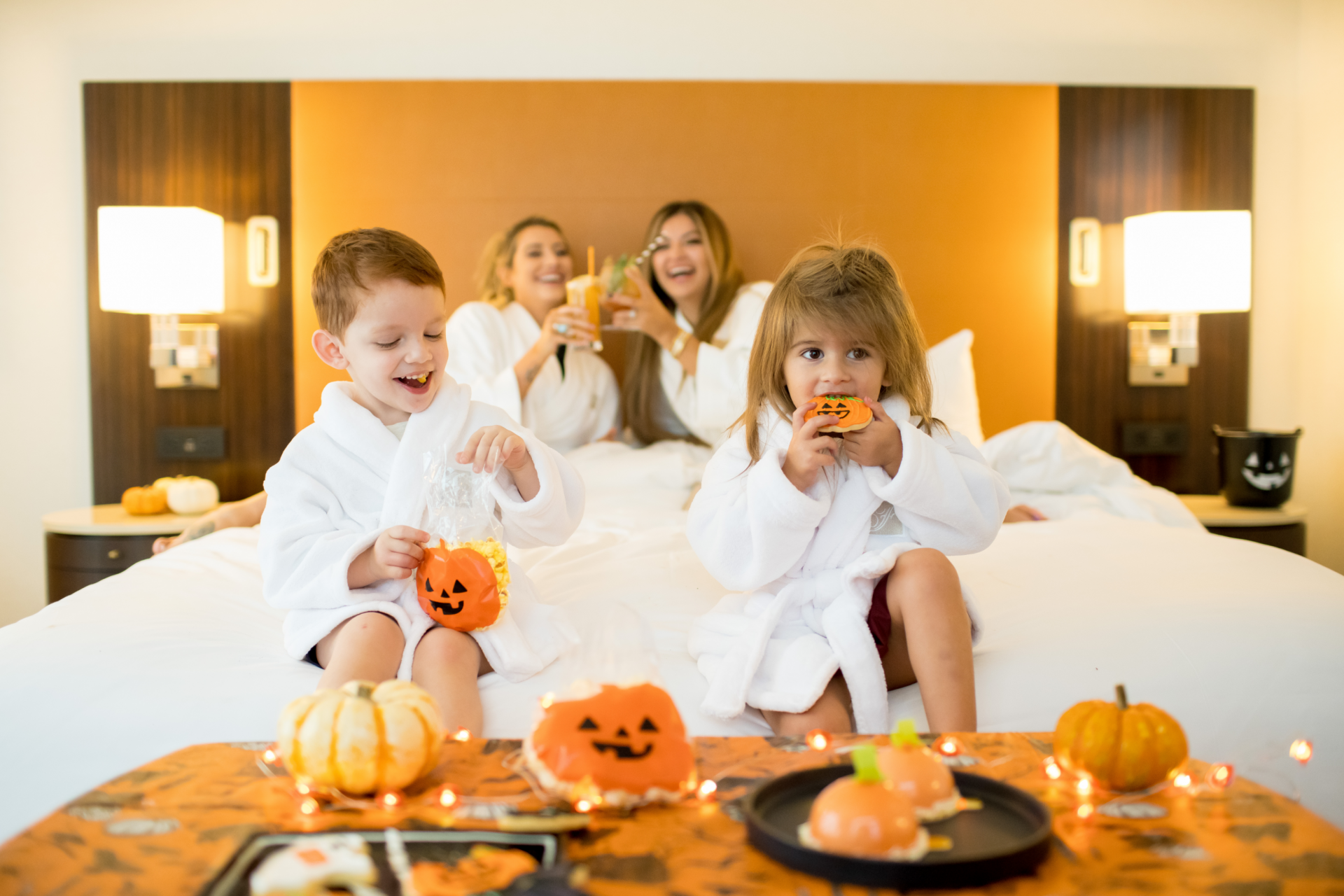 two children and two women enjoying halloween treats in the comfort of their hotel room