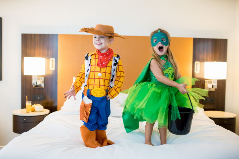two children wearing halloween costumes and standing on the hotel bed holding candy