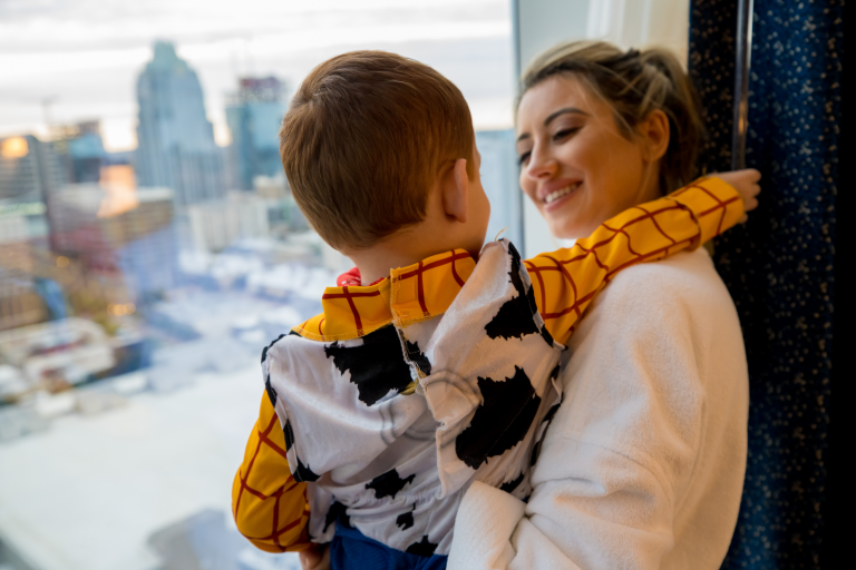 mother holding her son wearing a halloween costume while looking outside at the Austin skyline