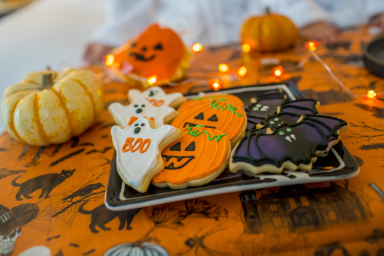 halloween cookies decorated as ghosts, pumpkins and bats sitting on a tray surrounded by pumpkins and halloween lights
